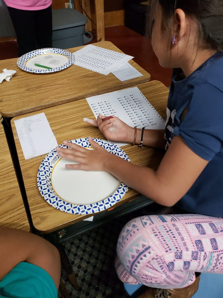 Kristin Wolfgang's students making  cuneiform letters in air drying clay.