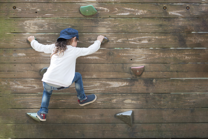 Girl being brave by climbing a rock wall